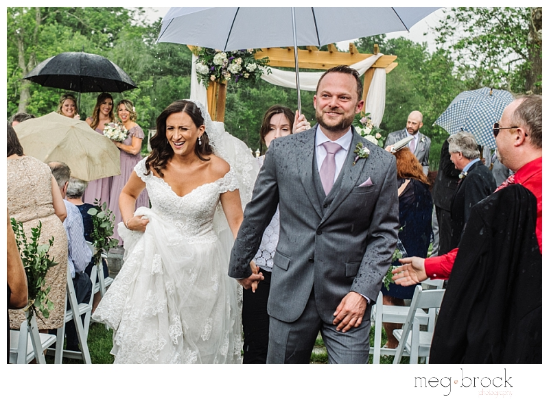 A bride and groom leave their wedding ceremony after some unexpected rain came down during their wedding at A bride and groom exit their wedding ceremony after their wedding at the Manor House at Prophecy Creek.