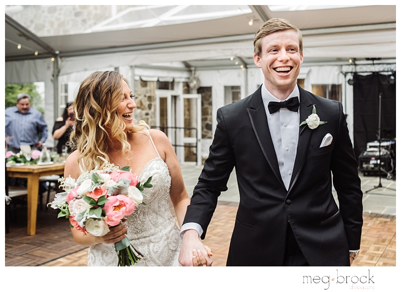 A happy bride and groom enter their their summer wedding at Welkinwier Estate in Pottstown, Pennsylvania.