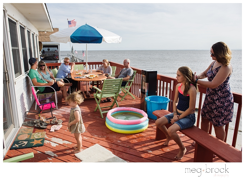 Family and friends of the brides sit outside and get ready for beach wedding at an elopement.